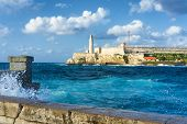 stock photo of malecon  - The famous castle of El Morro in Havana with a stormy weather and big waves in the ocean - JPG
