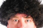 stock photo of mongol  - mongol man in a fuzzy hat with an odd look on his face - JPG