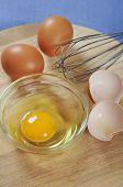 stock photo of chicken-wire  - Raw chicken eggs on wooden cutting board - JPG