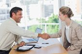 foto of interview  - Blonde woman shaking hands while having an interview in office - JPG