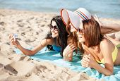 summer holidays, technology and beach concept - girls making self portrait on the beach