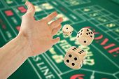 Hand Throwing Three Dices Over Casino Table