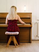Blond Woman Playing The Piano At Home