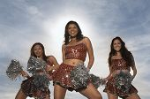 foto of pom poms  - Happy multiethnic cheerleaders dancing with pom poms against the sky - JPG