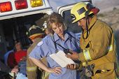 picture of paramedic  - View of fire fighters and paramedics assisting injured man - JPG