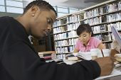 stock photo of shelving unit  - Two multiethnic students studying in the college library - JPG