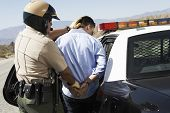 stock photo of policeman  - Rear view of a police officer guiding apprehended man into police car - JPG