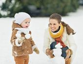 image of stroll  - Happy mother and baby making snowman in winter park - JPG