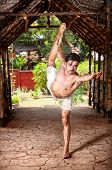 stock photo of natarajasana  - Yoga natarajasana dancer pose by fit man in white trousers on the drought earth in yoga shala Varkala Kerala India - JPG
