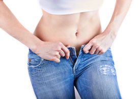 pic of bulging belly  - Overweight woman wearing jeans on a white - JPG