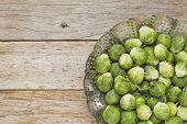 fresh Brussels sprouts in a metal steamer basket on wooden rustic table