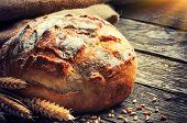 stock photo of whole-grain  - Freshly baked traditional bread on wooden table