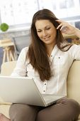 Young woman sitting on sofa with laptop on lap, browsing internet, smiling.