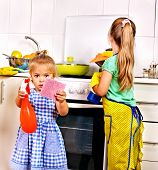 stock photo of pinafore  - Children cleaning  kitchen - JPG