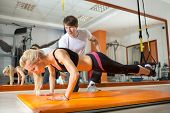 stock photo of pilates  - girl doing pushups with resistance band in the presence of a personal trainer - JPG