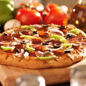 stock photo of take out pizza  - supreme italian pizza with pepperoni and toppings - JPG
