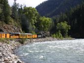 picture of chug  - Yellow train chugging along river in Colorado - JPG