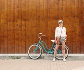 picture of mood  - Young sexy blonde girl with long hair in sunglasses standing near vintage green bicycle have fun and good mood looking in camera and smiling - JPG