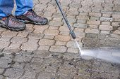 picture of pressure-wash  - Man cleaning his patio with a pressure washer - JPG
