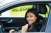 pic of seatbelt  - Closeup portrait young smiling happy attractive woman pulling on seatbelt inside black car - JPG