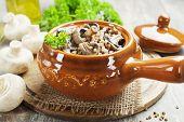 image of porridge  - Buckwheat porridge with mushrooms in a ceramic pot on the table - JPG