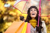 stock photo of rainy season  - Happy woman holding shopping bags and umbrella under autumn rain - JPG