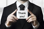 picture of grating  - businessman in black suit holding small white card thank you - JPG