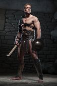 picture of strength  - Full length portrait of young attractive warrior gladiator with muscular body holding shield and axe - JPG