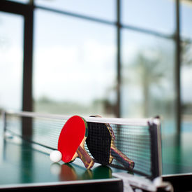 stock photo of ping pong  - Two table tennis or ping pong rackets and ball on a green table with net - JPG