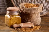 picture of mustard seeds  - Mustard seeds in bag and Dijon mustard in glass jar on wooden background - JPG
