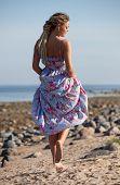 stock photo of dreadlock  - Happy young woman with dreadlocks walking along the seashore - JPG
