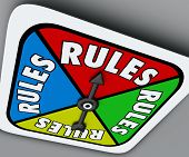 picture of spinner  - Rules word on a game board spinner to follow instructions or regulations as a competitor or player in a competition - JPG