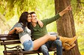 foto of sitting a bench  - Attractive young heterosexual couple sitting on a park bench - JPG