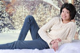 image of tween  - A pretty young tween happy in the snow wearing just a sweater and jeans - JPG