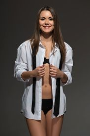 image of strip tease  - Sexy young Caucasian brunette woman wearing men white shirt - JPG