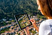 stock photo of albania  - Young woman tourist photographing with tablet Berat city from the castle mountain in Albania - JPG