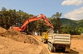 picture of dump_truck  - Exchavator track hoe loads a dump truck with top soil and loose dirt at a new commercial construction development project - JPG