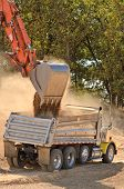 pic of track-hoe  - Large track hoe excavator filling a dump truck with rock and soil for fill for a new commercial development road construction project - JPG