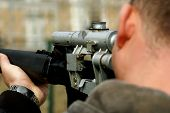 stock photo of sniper  - Looking down the barrel of a russian sniper rifle being held by a non identifiable man dressed in casual wear - JPG