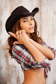 pic of cowgirls  - Beautiful young cowgirl gesturing and looking at camera while standing against the wooden background - JPG