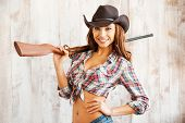 picture of cowgirls  - Beautiful young cowgirl carrying gun on her shoulders while standing against the wooden background - JPG