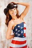 picture of cowgirls  - Beautiful young shirtless cowgirl adjusting her hat and covering herself by American flag while standing against the wooden background - JPG