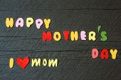 stock photo of mother-in-love  - Happy mothers day with i love mom message idea from colorful letter on wooden background woman hand cutting character to make gift for mother on happy day show feeling with mother love family - JPG