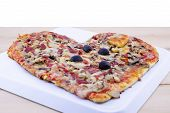 picture of olive shaped  - Heart shaped pizza on a plate on a wooden table - JPG