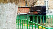 image of abandoned house  - Old broken pianoforte abandoned outdoors near the house  - JPG