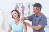 foto of shoulder muscle  - Doctor massaging his patient shoulders in medical office - JPG