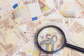 stock photo of fifties  - Closeup of fifty euro notes through magnifer background - JPG
