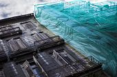 stock photo of scaffolding  - Scaffolding and old building on a renovation site - JPG