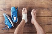 stock photo of ankle shoes  - Unrecognizable injured runner sitting on a wooden floor background - JPG
