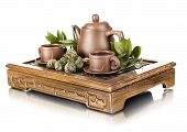 image of loam  - still life of the clay teapot and cup on wooden trivet on white background isolated - JPG
